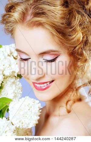 Summer, spring inspiration. Smiling young woman with natural make-up and beautiful curly hair holding white flowers. Beauty, fashion, cosmetics.