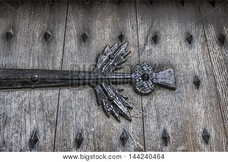 Scottish thistle shaped wrought iron detail painted black on old wooden door with metal studs