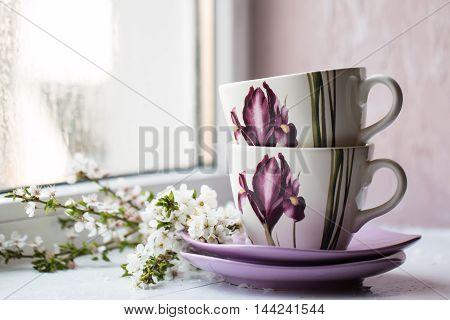 tea set a bouquet of spring flowers near the window