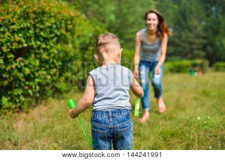 Happy Mother and son playing with bubbles at summer day.