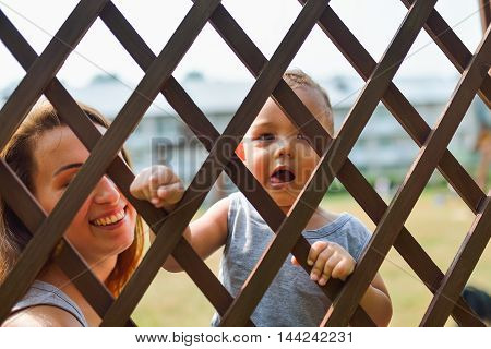 Portrait of cute child looking through fence, happy smiling mother at background.