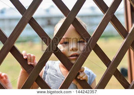 Sad and lonely child looking out through fence. Children stress and negative emotions