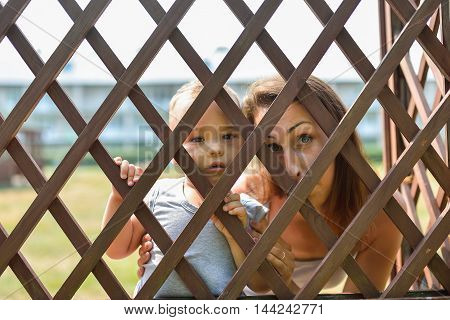 Cute child and his mother have fun looking through fence.