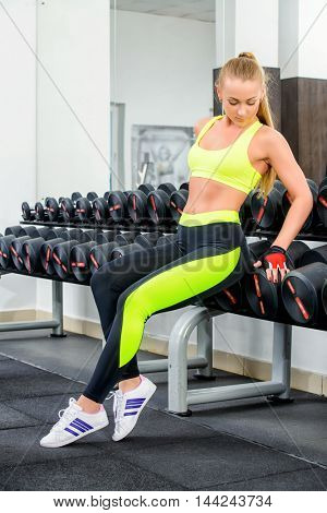 Slender young woman with beautiful athletic body doing exercises with dumbbells. Fitness, bodybuilding. Healthcare.