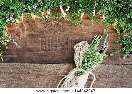 Christmas tree pine branches and decorative lights with silverware over a rustic background of barn wood. Image shot from overhead.