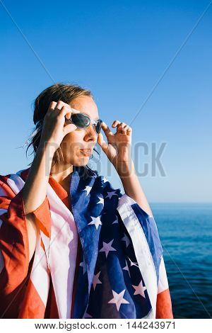Portrait of young woman with wet hair and american flag on shoulders wearing goggles against of bright sea blending with clear sky