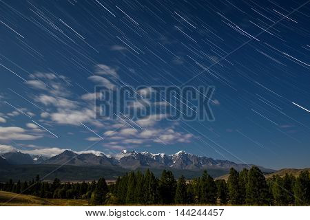 Beautiful night landscape with clouds and traces of the stars in the night sky on the background of the mountains with snowy peaks and the forest shot with a long exposure