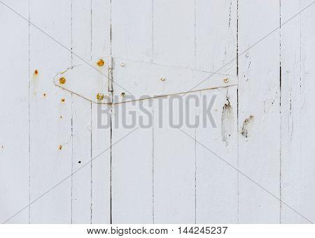White wooden door hinge and rusty screws