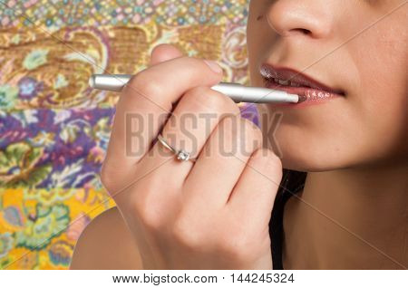 Girl paints her lips. pencil. in a pale pink color