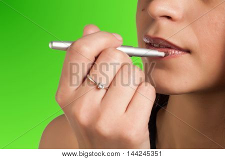 Green background Chroma Key. Girl paints her lips. pencil. in a pale pink color