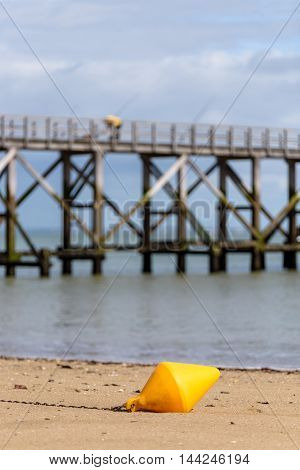 Orange buoy on the beach in Noirmoutier, pier in the background
