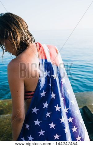 Rear view of unrecognizable woman with wet hair wearing american flag on pier against of sea