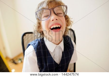 Little cheerful schoolboy. Curly boy in huge glasses light-heartedly laughs. It is a disciple of an elementary school.