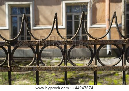 Old iron rusty lattice against the background of houses