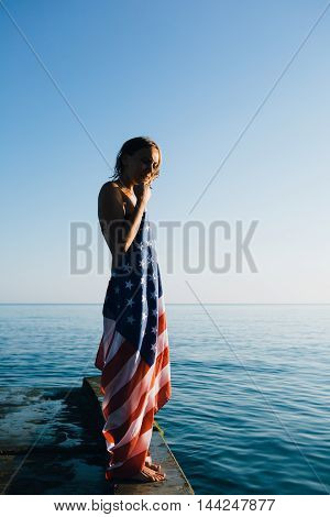 Side view of young woman with eyes closed standing on wet pier with american flag.Blue sky blending with sea.