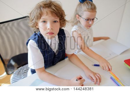 Two small disciples of an elementary school sit at school desk. On a school desk there are textbooks and school accessories. Boy looks into a camera with a serious views. Schoolgirl writes something.