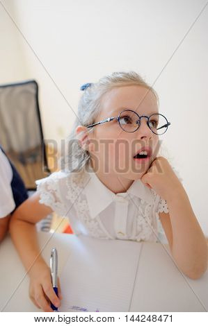 Small schoolgirl of an elementary school sits at a school desk in thoughtfulness. Open copybook and school supplies are on the desk. Girl rested her head on his hand and looking dreamily somewhere.