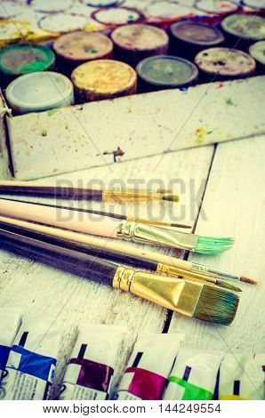 Artist paint brushes, oil paint tubes and gouache paint jars on white wooden background. Brush, paint, artistic. Tools for creative work. Back to school. Paintings Art Concept. Selective focus.