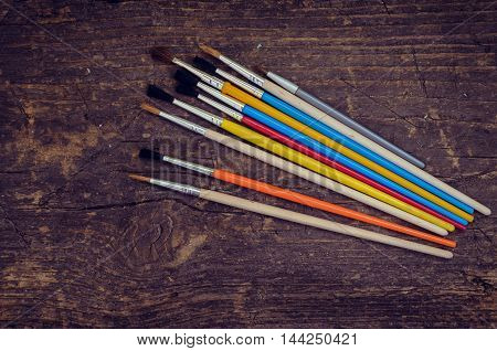 Paint brushes on a wooden background. Brush, paint, artistic. Tools for creative work. Watercolor paintbox. Back to school. Kids painting concept. Children art. Top view. Copy space.