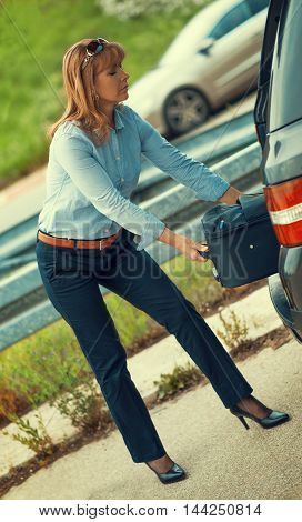 Business travel.Mature woman take suitcase from car.