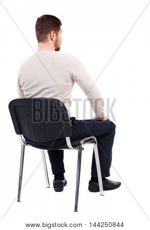 back view of business man sitting on chair.  businessman watching. Rear view people collection.  backside view of person.  Isolated over white background. The bearded man in a white warm sweater sits