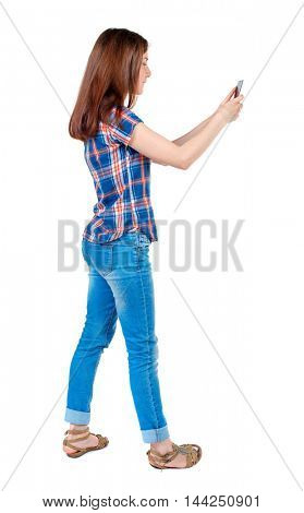 back view of standing young beautiful  woman  using a mobile phone. girl  watching. Rear view people collection.  backside view of person.  Isolated over white background.  Girl in plaid shirt