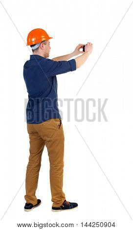 Backview of an engineer in construction helmet stands and using photo camera. Standing young guy. Rear view people collection.  backside view of person.  Isolated over white background.  a man in a