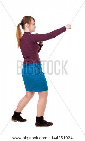 skinny woman funny fights waving his arms and legs. Isolated over white background. Girl with red hair tied in a pigtail boxing.