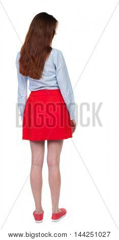 back view of standing young beautiful  woman.  girl  watching. Rear view people collection.  backside view of person. Long-haired brunette in red skirt looks down sideways.