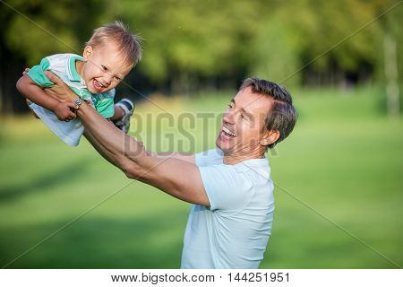 Young father and toddler son having fun in summer park