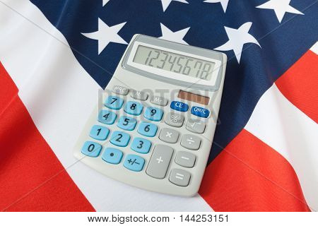 Studio Shot Of Ruffled National Flag With Calculator Over It - Usa