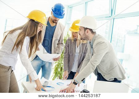 Image of four successful business partners working at meeting in office.Construction workers checking the architectural plans before they start the building project.
