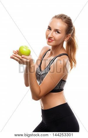 Young beautiful sportive girl posing, holding green apple over white background. Copy space.