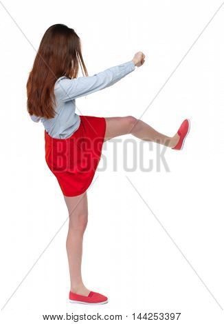 skinny woman funny fights waving his arms and legs. Isolated over white background. Long-haired brunette in red skirt swung a leg.