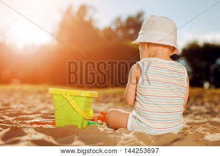 Baby boy playing on the sandy beach near the sea.