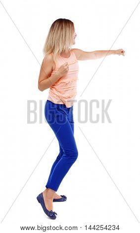 back view of standing girl pulling a rope from the top or cling to something. Isolated over white background. The blonde in a pink shirt punches.