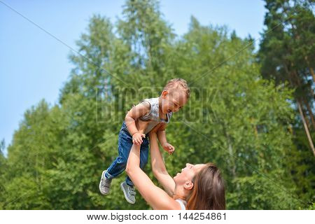 Happy family outdoors. mother throws baby up, laughing and playing in summer on the nature.