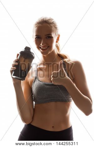 Young beautiful sportive girl holding bottle, posing over white background. Copy space.