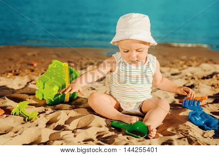 Baby boy playing with beach toys, close up