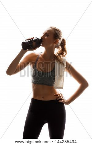 Young beautiful sportive girl holding bottle and towel, posing over white background. Copy space.