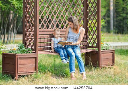 Mother and son sitting on a bench in a park and reading a book.