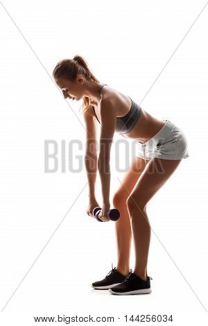 Young beautiful sportive girl training with dumbbells over white background. Copy space.
