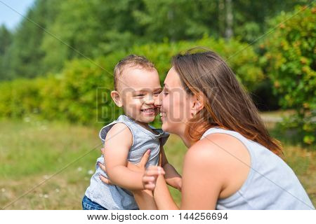 Happy family having fun outdoors. Mother and baby rubbing noses and laugh. Positive emotions.