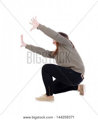 back view of woman protects hands from what is falling from above. Isolated over white background. A girl in a gray jacket protects hands from then on the right