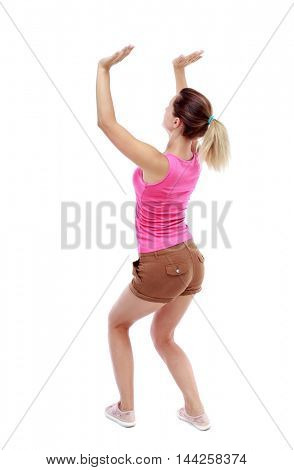 back view of woman protects hands from what is falling from above. Isolated over white background. Sport blond in brown shorts pushing something up.