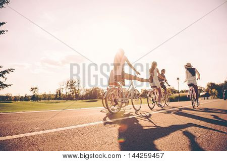 Enjoying nice summer day together. Low angle view of young people riding bicycles along a road and looking happy