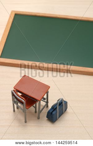 Miniature blackboard, desk, and school bag on wood.