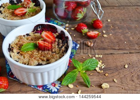 Berry crumble with oatmeal and almonds on wooden background
