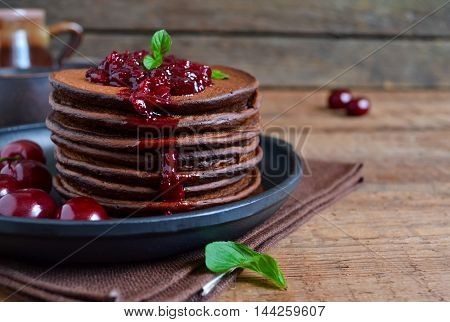 chocolate pancakes with berry jam for breakfast on a wooden background