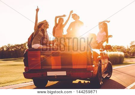 Ready to adventures. Group of young cheerful people dancing and playing guitar while enjoying their road trip in pick-up truck together